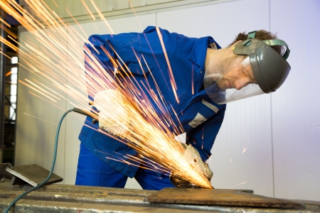 metalworking: A construction worker using an angle grinder producing a lot of sparks