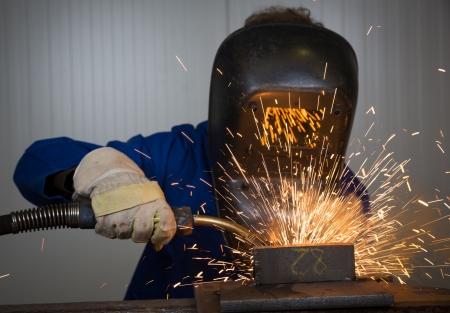Man with welding helmet welding steel Stock Photo