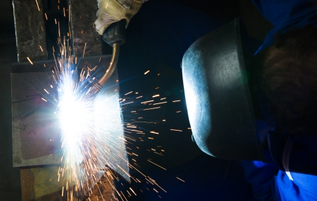 acetylene: A worker with a welding helmet welding steel seen from above creating many sparks Stock Photo