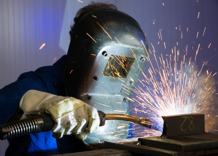 Man with welding helmet welding steel photo