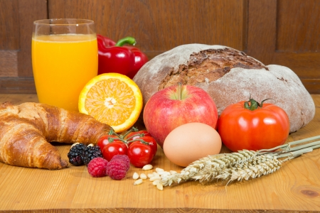 Different types of food such as bread, a tomato, apple, pine seeds, raspberry and a croissant as well a glass of orange juice photo