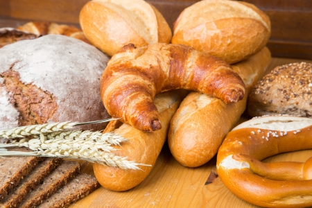 bakery products: Different types of bakery products such a a loarf of bread, pretzel, whole grain bread and buns