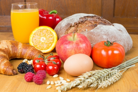 wholemeal: Different types of food such as bread, a tomato, apple, pine seeds, raspberry and a croissant as well a glass of orange juice