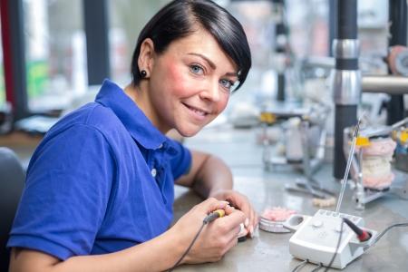 articulator: Dental technician applying wax to a mold