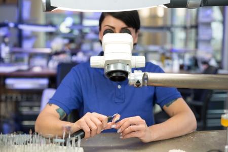 Dental technician grinding or polishing under a microscope photo