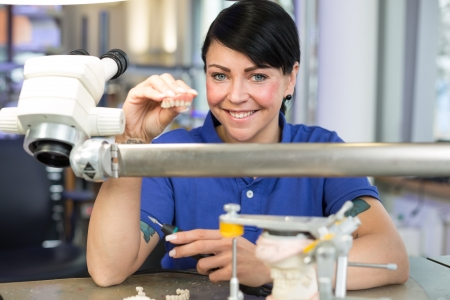 Dental technician presenting a prosthesis into the camera photo