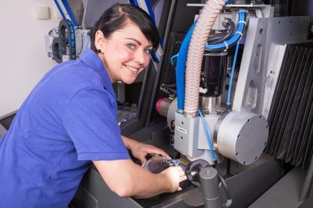 technicians: Dental technician working on a milling machine