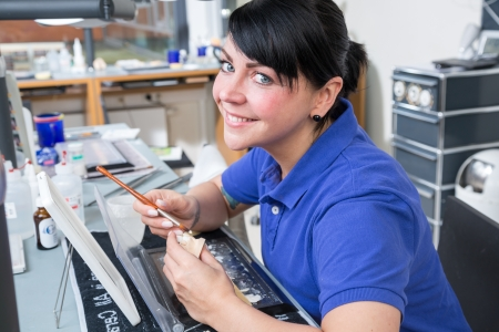 Dental technician applying ceramics to a mold Stock Photo