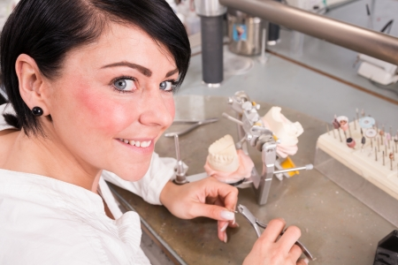 Technician in a dental lab working on a prosthesis photo