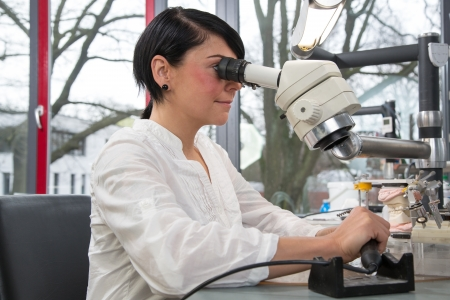 Technician in dental lab working under a microscope photo