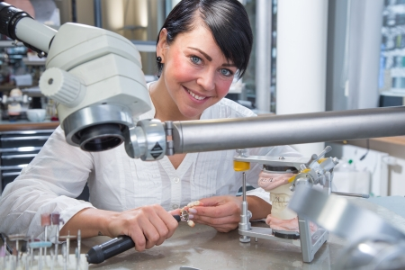 Technician in dental lab working under a microscope Stock Photo