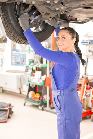 Woman repairing the brakes of a car on hydraulic lift Stock Photo