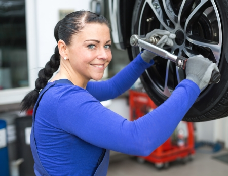 automobile repair shop: Mechanic changing the wheel on a car hydraulic lift Stock Photo