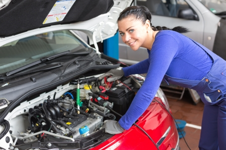 car shop: Mechanic repairing the motor or electric parts of a car in a garage Stock Photo