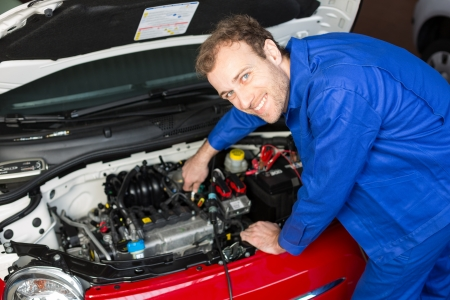 auto garage: Mechanic repairing the motor or electric parts of a car in a garage Stock Photo