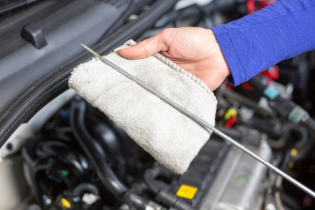 auto shop: Car mechanic checking the oil of a car Stock Photo