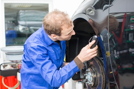 car shop: Car mechanic repairs the brakes of an automobile on a hydraulic lift