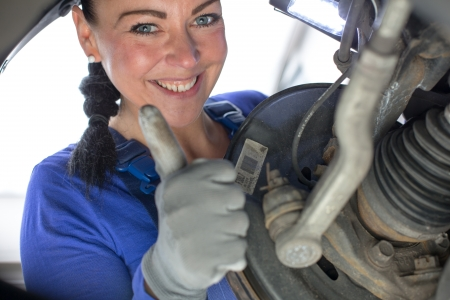 motor mechanic: Car mechanic repairs the brakes of an automobile on a hydraulic lift