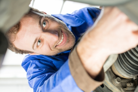 Car mechanic repairs the brakes of an automobile on a hydraulic lift photo