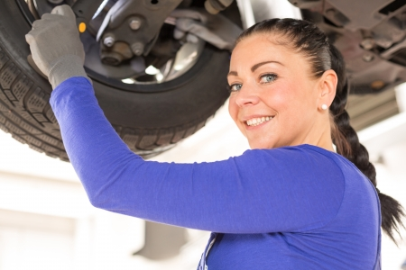 Woman repairing the brakes of a car on hydraulic lift Stock Photo - 18691709