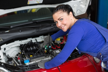 car maintenance: Mechanic repairing the motor or electric parts of a car in a garage Stock Photo