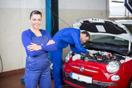 Car mechanic posing in garage photo