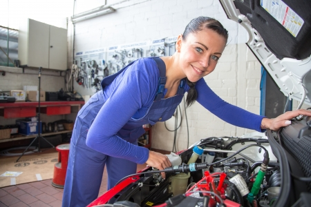 Car mechanic repairing a automobile in a garage or workshop photo