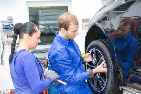 hydraulic: Two mechanics changing a wheel of a car on a hydraulic lift Stock Photo