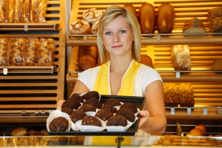 Saleswoman in bakery or confectionery present a tablet of rum balls photo