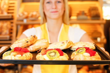 Bakery shopkeeper presents pastry and cakes