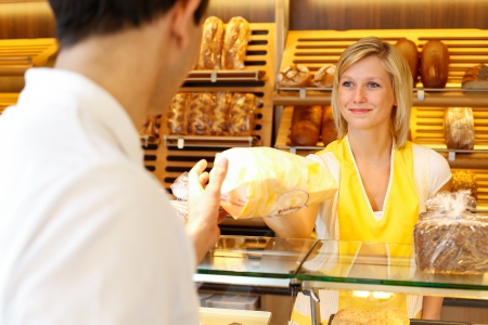 Bakery shopkeeper hands bag of bread over to customer