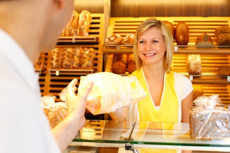 shopkeeper: Bakery shopkeeper hands bag of bread over to customer