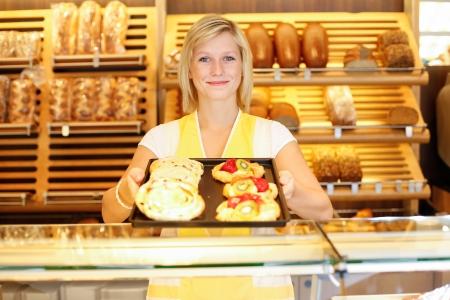 bread shop: Negoziante in forno presenta un tablet pieno di dolci