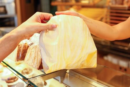 bolsa de pan: Panadería comerciante manos bolsa de pan a los clientes Foto de archivo