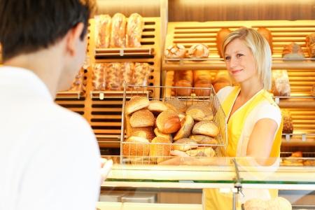 breadbasket: Shopkeeper presents a breadbasket to customer Stock Photo