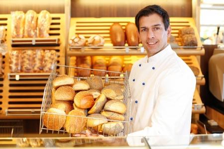 retailer: Shopkeeper presents a breadbasket to customer Stock Photo