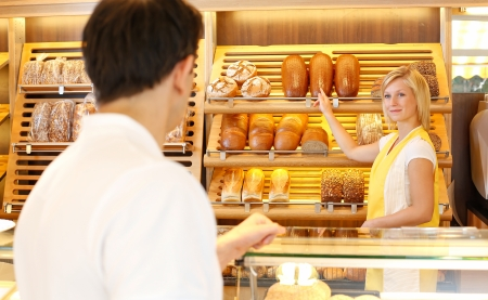 saleslady: Bakery shopkeeper shows bread to customer