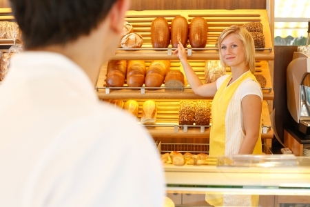pastry shop: Bakery shopkeeper shows bread to customer