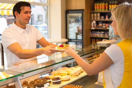 Bakery shopkeeper gives pastry to customer