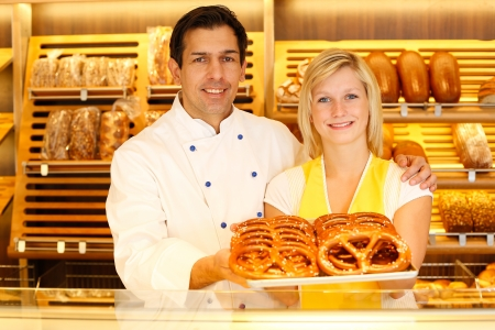 Shopkeeper and baker in Bakery or bakers shop present a tablet full of pretzels