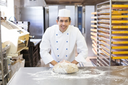 bakery products: Baker kneading dough in a bakehouse or bakery