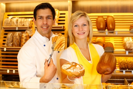 Bakery shopkeeper and baker present different types of pastry in shop photo