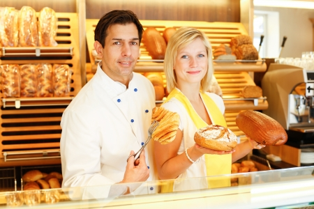 bakery store: Bakery shopkeeper and baker present different types of pastry in shop Stock Photo