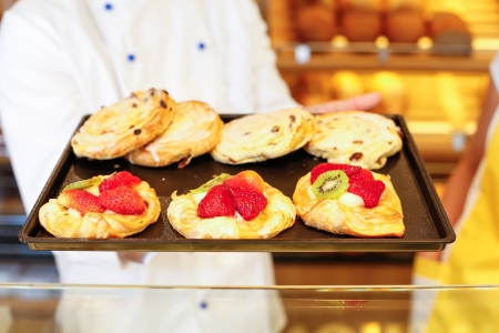 pastry shop: Bakery shopkeeper and baker present different types of pastry in shop Stock Photo