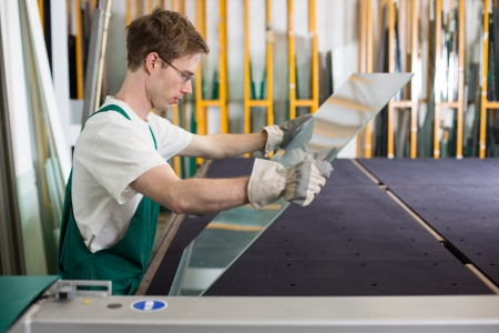 glazier: Worker in glaziers workshop or glass warehouse handling glass Stock Photo