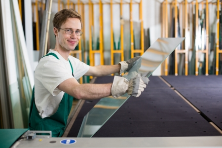 Worker in glaziers workshop or glass warehouse handling glass Stock Photo