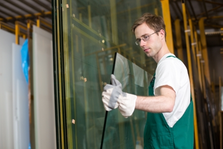 Worker in glaziers workshop, warehouse  or storage handling glass