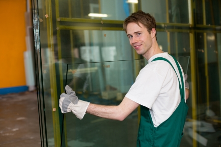 Worker in glaziers workshop, warehouse  or storage handling glass photo