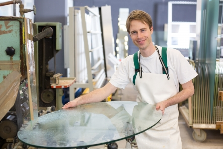 glasscutter: glazier deburrs a glass on grinding machine in workshop  Stock Photo