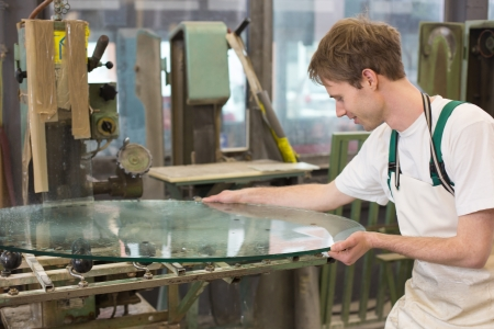 glazier: glazier deburrs a glass on grinding machine in workshop  Stock Photo